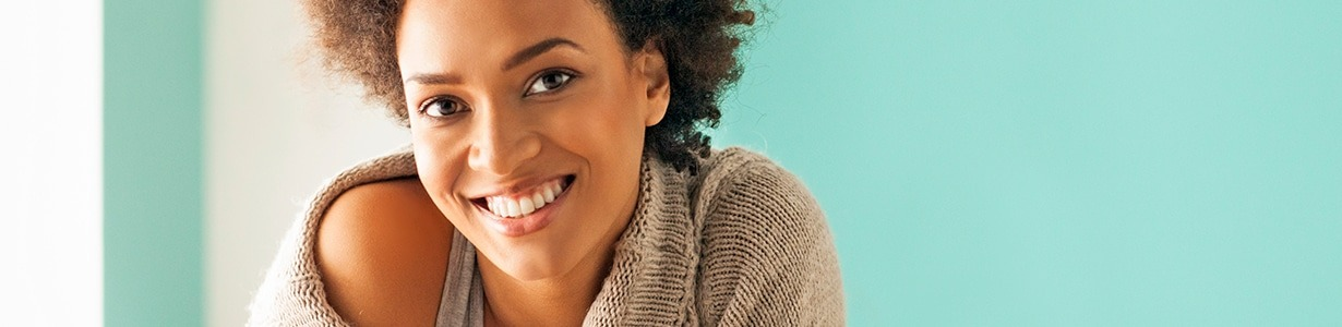 African American woman smiling against a teal blue background