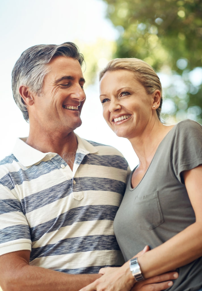 Middle age couple with white teeth smiling outside